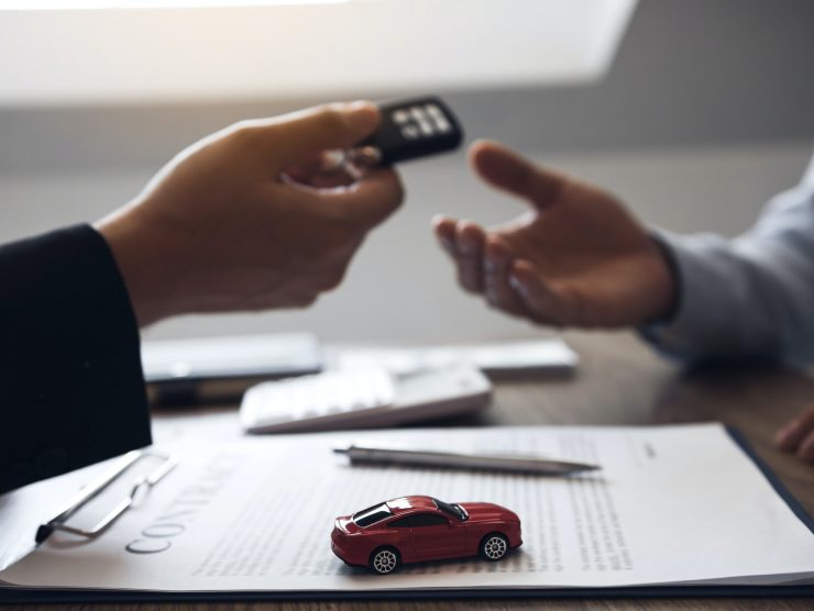 car salesman is presenting the new car keys to the car buyer at the showroom