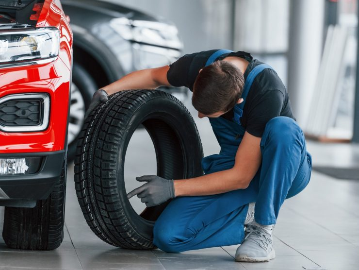 Man in uniform changing tire of automobile. Conception of car service
