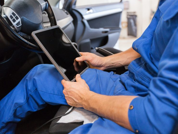 mechanic man with tablet pc making car diagnostic